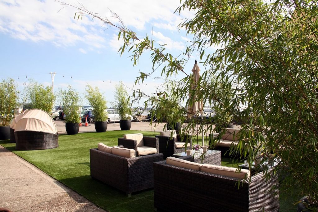 Dressing an outside space with artificial turf and large bamboos